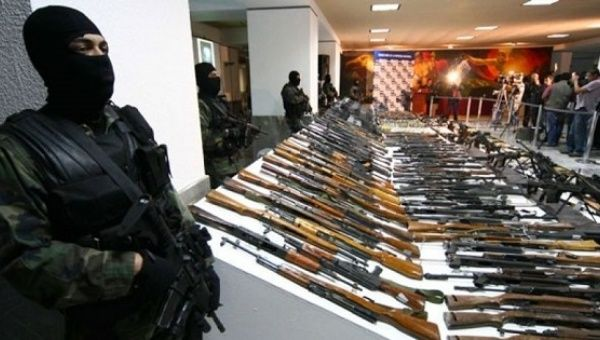 Soldiers stand guard near seized weapons during a previous news conference at the Defense Headquarters in Mexico City.