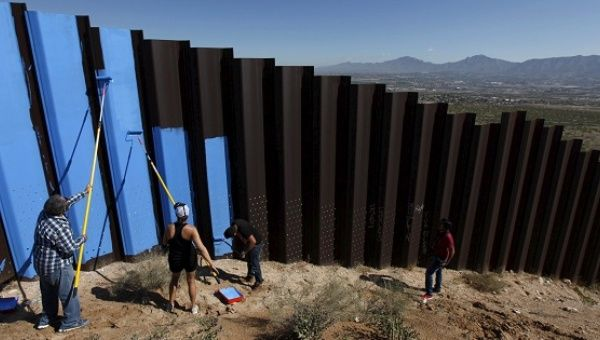 "Artist Ana Teresa Fernandez and members of Border/Arte ""erase"" the border fence by painting it sky blue."