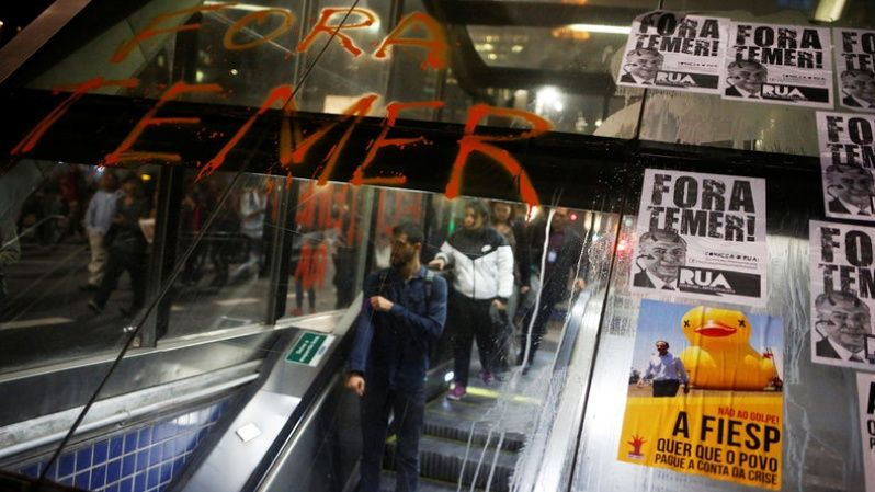 People go down the escalator in front of a phrase and posters with the image Brazil