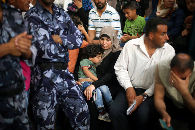 A woman carries her child as she waits for a travel permit to cross into Egypt through the Rafah border crossing after it was opened by Egyptian authorities, in the southern Gaza Strip June 4, 2016.