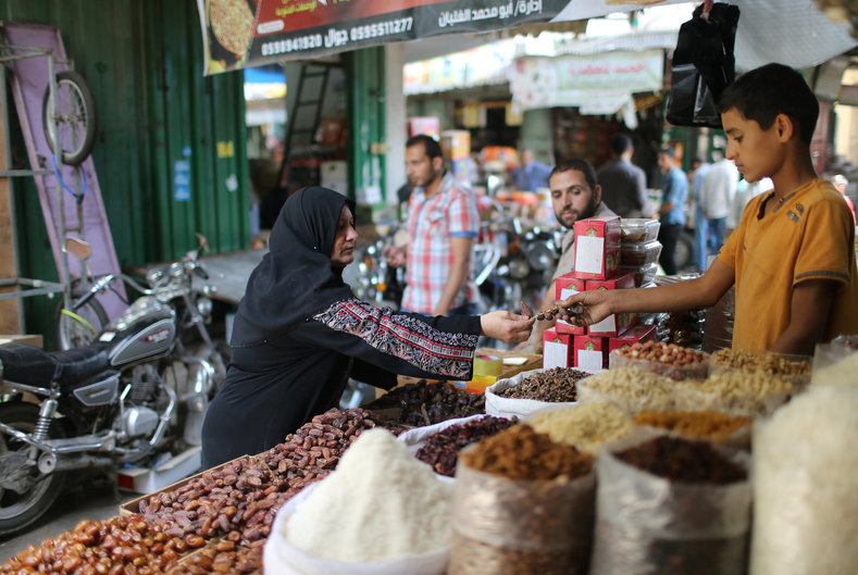 Palestinians shop in a market ahead of the Muslim fasting month of Ramadan in Khan Younis in the southern of Gaza Strip June 5, 2016.