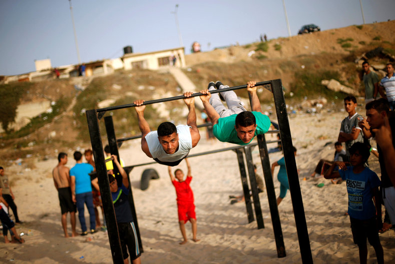 Members of Bar Palestine team demonstrate their street workout skills during a training session on a beach in Gaza City, June 3, 2016.