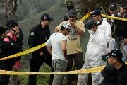 Colombian police look at the human remains found in a mass grave.
