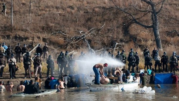 Police fire teargas at people in the water of a river during a protest against the Dakota pipeline, Nov. 2, 2016.