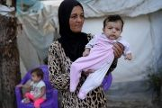 A Syrian refugee poses with her baby in front of their tent in Yayladagi refugee camp in Hatay province, Turkey, Oct. 15, 2016.