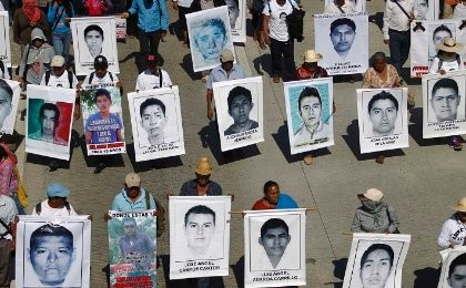Relatives hold pictures of missing students from the Ayotzinapa Teacher Training College Raul Isidro Burgos, during a demonstration in Chilpancingo, Guerrero December 2, 2014.