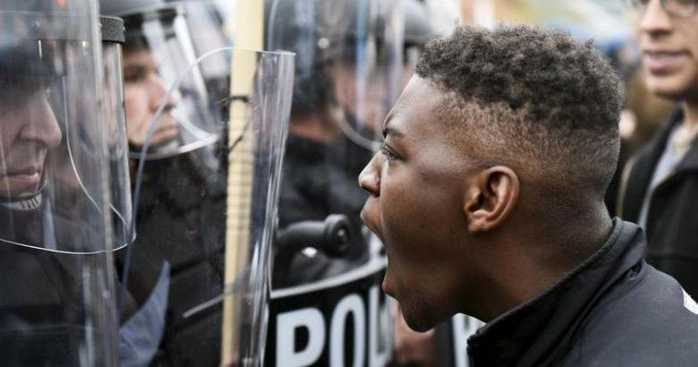 A demonstrator confronts police near Camden Yards during a protest against the death in police custody of Freddie Gray.