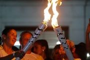One athlete relays the Olympic torch to another in the streets of Sao Jose dos Campos
