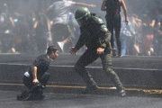 A policeman tries to detain a protester.