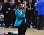 National anthem singer Denasia Lawrence kneels as she performs prior to the NBA game between the Miami Heat and the Philadelphia 76ers, Oct. 21, 2016.