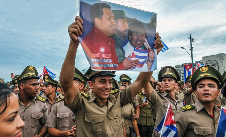 Cuban soldiers hold up a poster of former Venezuelan President Hugo Chavez, Fidel Castro and Bolivian leader Evo Morales during anniversary celebrations.