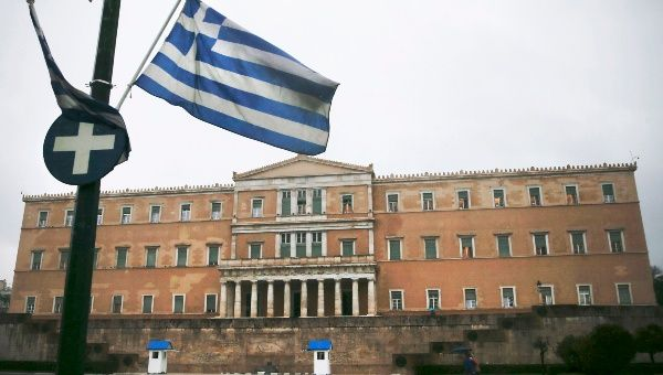 A Greek national flag flies in front of the parliament building in Athens.