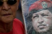 A supporter of holds an image of Venezuela's late President Hugo Chavez during a gathering in Caracas, Venezuela October 1, 2016.
