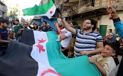 People carry Free Syrian Army flags in the rebel-held besieged al-Shaar neighborhood of Aleppo, Syria Oct. 20, 2016.