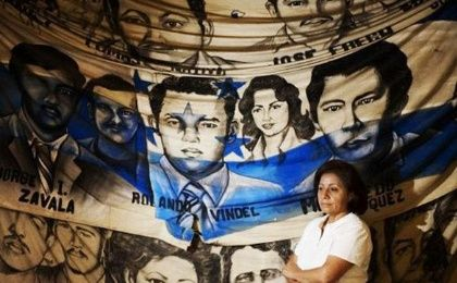 Bertha Oliva, founder and director of COFADEH whose husband was disappeared by Battalion 316, stand in front of a banner of the disappeared.