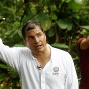 Ecuadorean President Rafael Correa raises his oil-covered hand covered having placed it in a contaminated area in the Amazon.