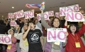 People standing in the public gallery of the Kagoshima Prefectural Assembly on Friday protest its decision to approve the restart of two reactors at the Sendai nuclear power plant. Gov. Yuichiro Ito approved the restart later the same day. (Photo: KYODO)