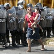 A woman and her daughter walk past a riot police officers in Managua City, Nicaragua.