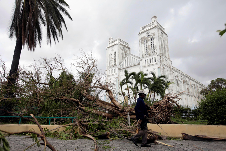 A man carrying branches from fallen trees walks next to the Cathedral after Hurricane Matthew in Les Cayes, Haiti, Oct. 5, 2016.