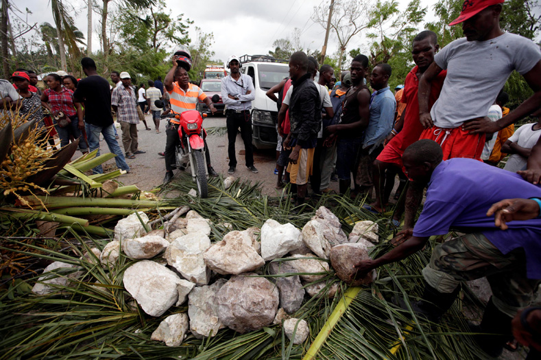 A man puts a rock on a barricade set up on the road to protest against the lack of assistance after Hurricane Matthew in Cavaillon, Haiti, Oct. 6, 2016.