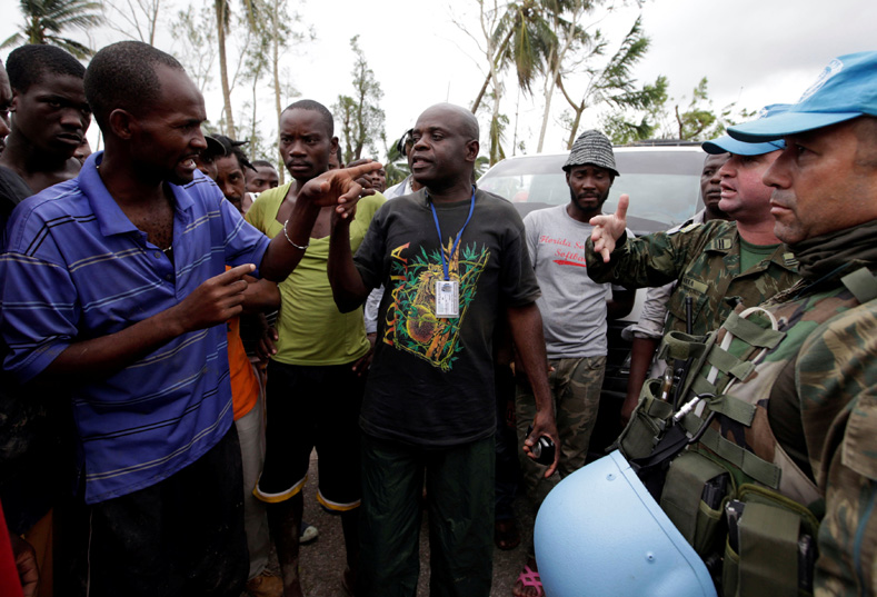 Brazilian peacekeepers speak to a resident who set up a barricade on the road to protest against the lack of assistance after Hurricane Matthew in Cavaillon, Haiti, Oct. 6, 2016.