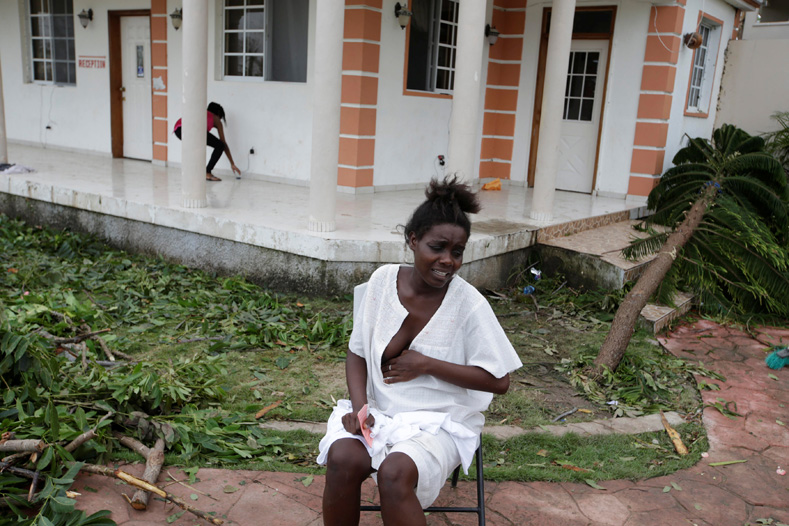 Emma Etienne sits in pain as she waits to find a doctor to give her a cesarean section to deliver her baby after she was sent back from the hospital, at a temporary shelter in Hotel Villa Mimosa following Hurricane Matthew,in Les Cayes, Haiti, Oct. 6, 2016.