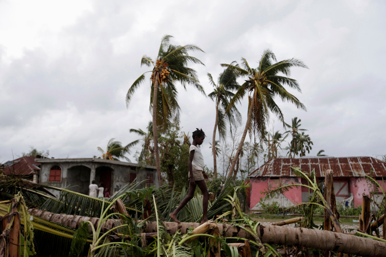 A girl walks on a tree damaged by Hurricane Matthew in Les Cayes, Haiti.