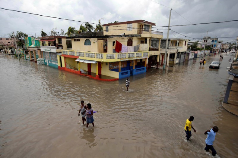 People walk in a flooded area after Hurricane Matthew in Les Cayes, Haiti, Oct. 5, 2016.