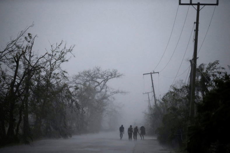 People walk on the road as rain falls during Hurricane Matthew in Les Cayes, Haiti, Oct. 4, 2016.