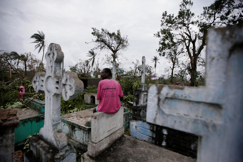 A man sits on a tombstone as he watches other clearing trees after Hurricane Matthew in Les Cayes, Haiti, Oct. 6, 2016.
