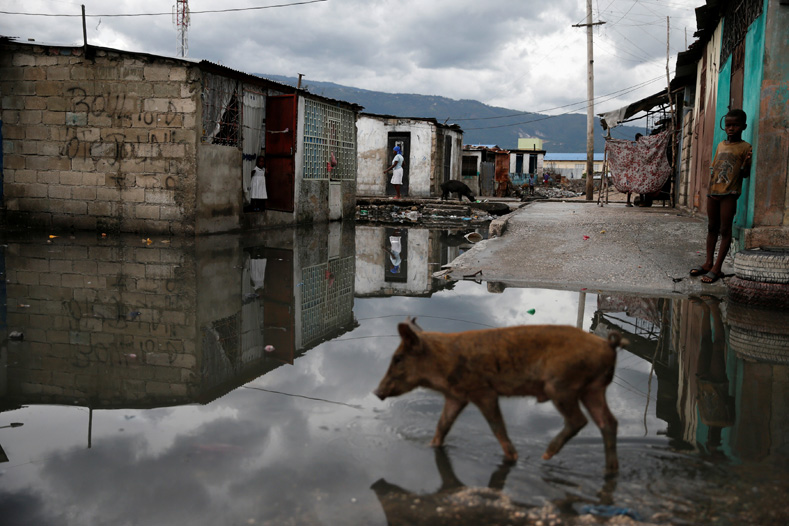 A boy stands near a flooded street after Hurricane Matthew passes Cite-Soleil in Port-au-Prince, Haiti, Oct. 5, 2016.