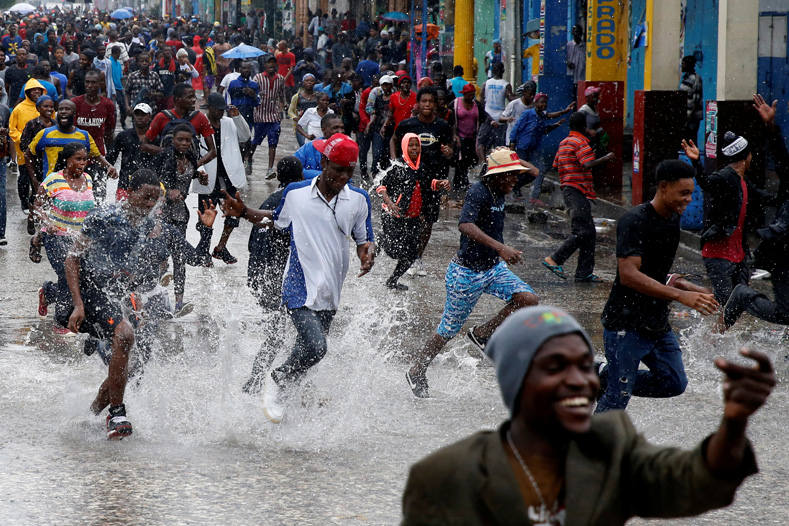 Supporters of Fanmi Lavalas political party splash around in water on a flooded street as they take part in a gathering while Hurricane Matthew passes in Port-au-Prince, Haiti, Oct. 4, 2016.