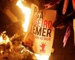 Members of Brazil's Landless Workers' Movement burn a poster with the image of Brazil's Interim President Michel Temer during a protest in Sao Paulo, Brazil, May 12, 2016.