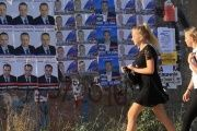 Girls walk past election campaign posters of candidates running for deputies, ahead of the parliamentary elections in Sevastopol, Crimea, Sept. 16, 2016.