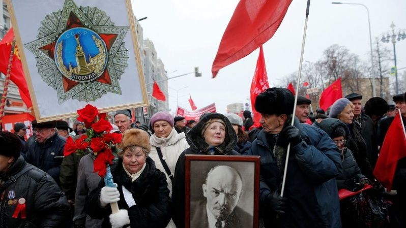 Russian communist supporters carry flags and a portrait of Soviet state founder Vladimir Lenin on the 99th anniversary of the 1917 October revolution, Nov. 7, 2016.