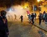 People try to move away from a gas cloud during a protest against the election of Republican Donald Trump as President of the United States in Portland, Oregon.