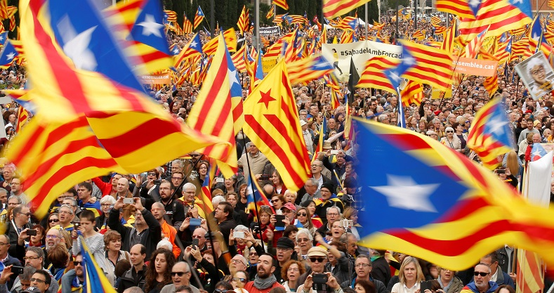 "Thousands wave the Catalan flag, known as ""Esteladas"", during a gathering to protest against legal challenges made by Spain"