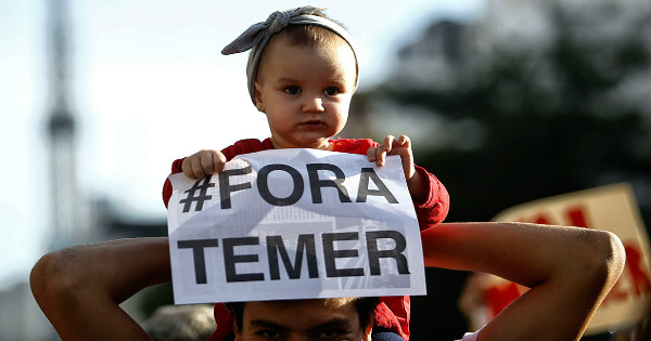 A child holds a sign reading 'Temer out' in a protest against Brazil's acting president Michel Temer in Sao Paulo