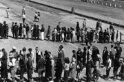 Newly-arrived evacuees lined up outside a Japanese-American internment center at the Tanforan Assembly Center in San Bruno, CA, in 1942.