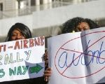 Two women protesters hold anti-Airbnb posters, demanding the company leave occupied Palestine.