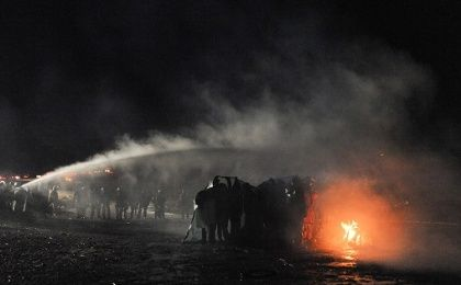 Police use a water cannon to put out a fire started by protesters during a protest against plans to pass the Dakota Access pipeline near the Standing Rock Indian Reservation, near Cannon Ball, North Dakota.