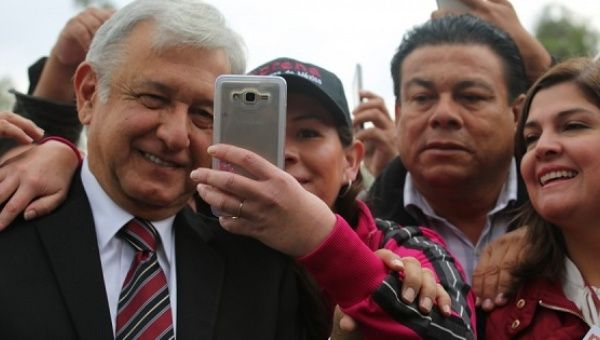 Andres Manuel Lopez Obrador takes a selfie with supporters during Morena