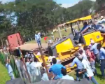 A bulldozer is forcing the entrance of the campus occupied by students, sweeping away the fence as well as protesters.