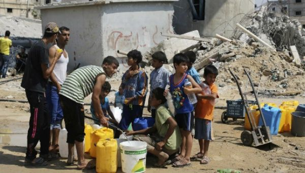 Palestinian children collect water in Khan Yunis, in the southern Gaza Strip, during the 2014 Israeli Invasion.