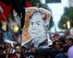 A demonstrator holds a banner with a drawing representing Michel Temer in Rio de Janeiro, Brazil, Nov. 25, 2016.