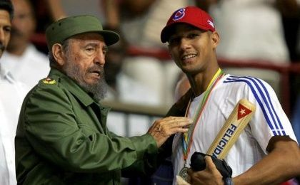 Then-Cuban President Fidel Castro (L) hands out a baseball bat to Cuban player Yulieski Gourriel in Havana in this March 21, 2006 file photo.