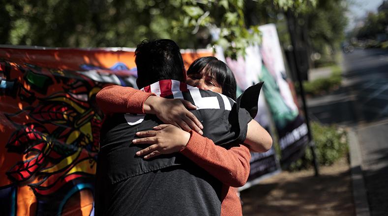 Dos personas se abrazan en medio del llanto por la muerte del líder de la Revolución Cubana, en la embajada cubana en Santiago de Chile.