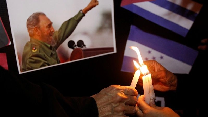 People place candles beside a picture of Fidel, as part of a tribute, following the announcement of the death of Cuban revolutionary leader Fidel Castro, in Tegucigalpa, Honduras Nov. 26, 2016.