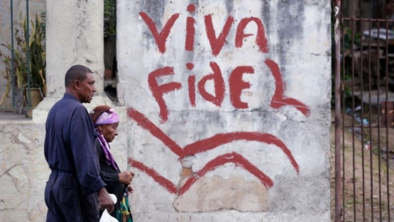 "People walk past a graffiti that reads ""Long live Fidel"" in Havana, Cuba Nov. 26, 2016."