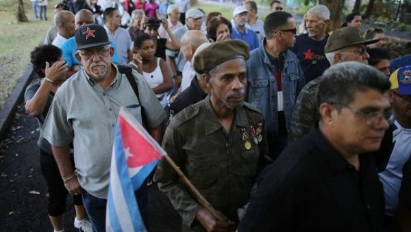 People stand in line to pay tribute to Cuba